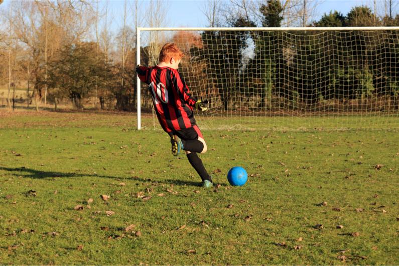 football boy practising kick goal