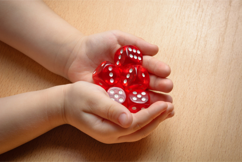 Child's hands holding dice