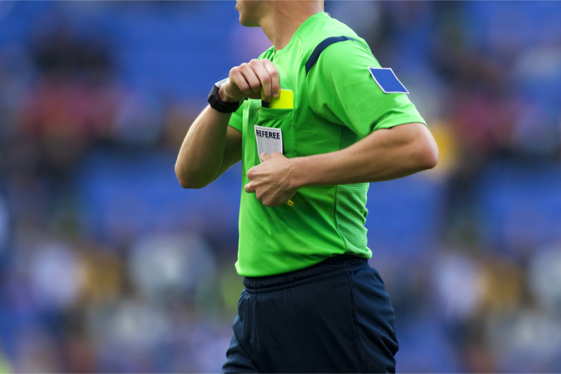 Soccer referee about to show a yellow card to a player during a match