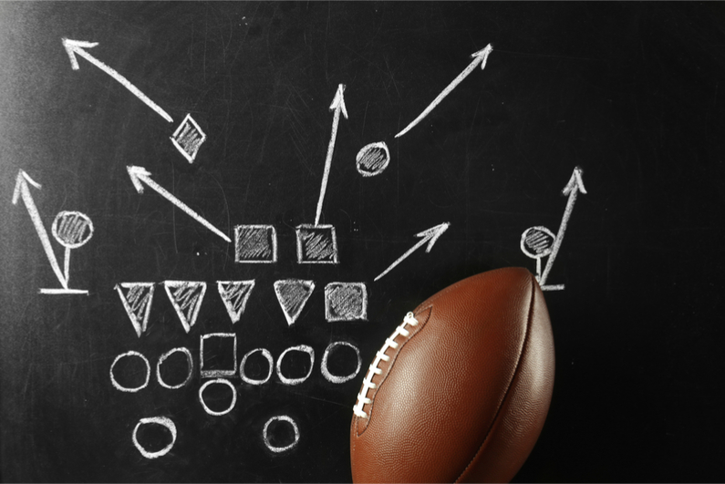 American football defense diagram in chalk on blackboard