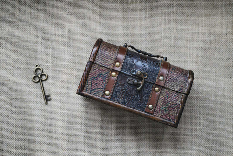 Vintage loot box and key on sackcloth background .