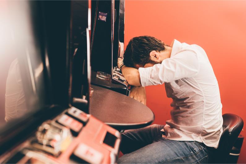 Man leaning on gambling machine