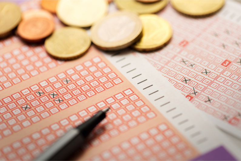 Lottery tickets with coins and pen