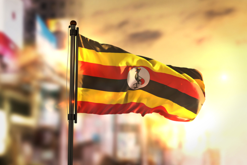 Uganda Flag Against City Blurred Background At Sunrise Backlight 3D Rendering