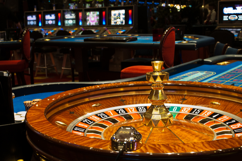 Golden Casino theme. High contrast image of casino roulette, poker game, dice game, poker chips on a gaming table.