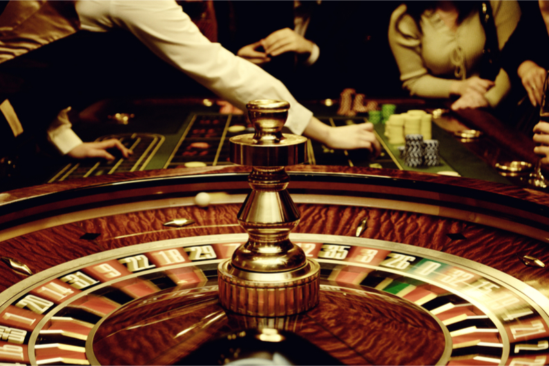 People play casino games: gold spinning roulette with motion of players, croupier (dealer) and roulette in a modern casino