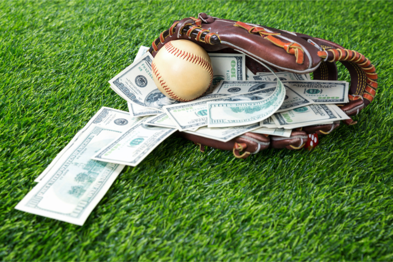Close up of baseball in a Glove with dollar bills in concept of getting money with bets in baseball