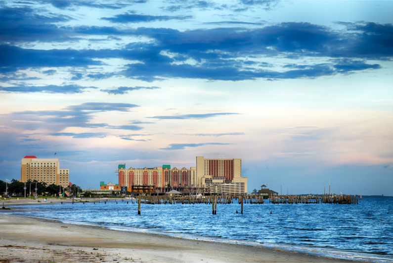 Biloxi, Mississippi, casinos and buildings along Gulf Coast shore at sunset