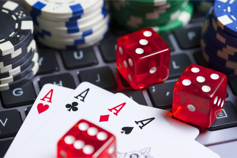 Casino chips, cards and dice stacking on a laptop