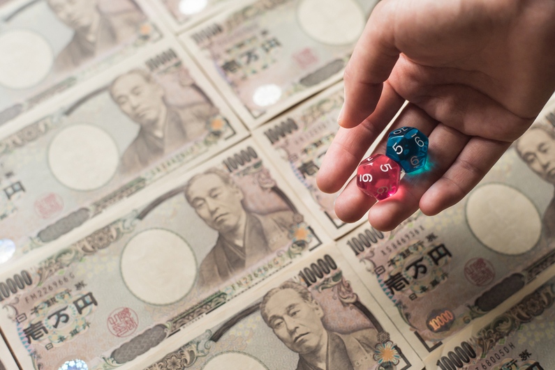 Hand holding dice against background of Japanese currency