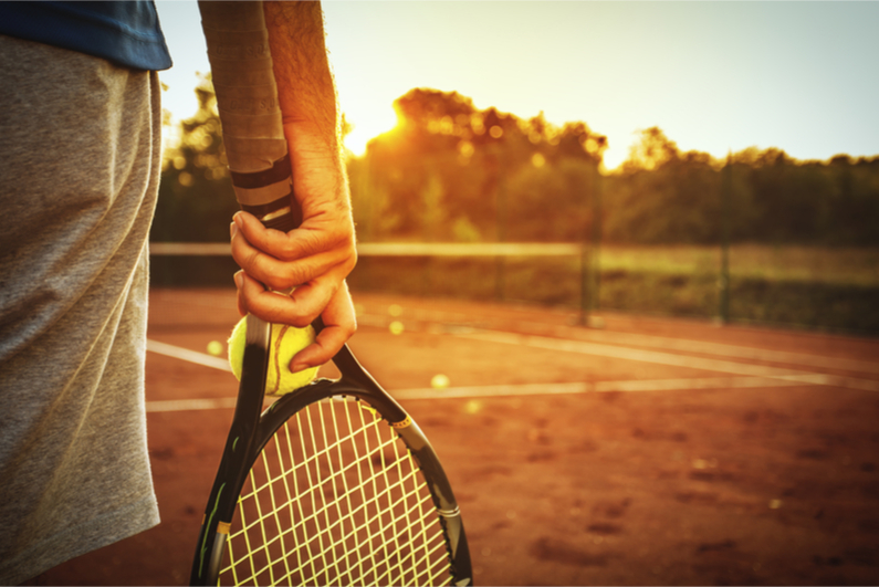Hand holding tennis ball and racquet on clay court background
