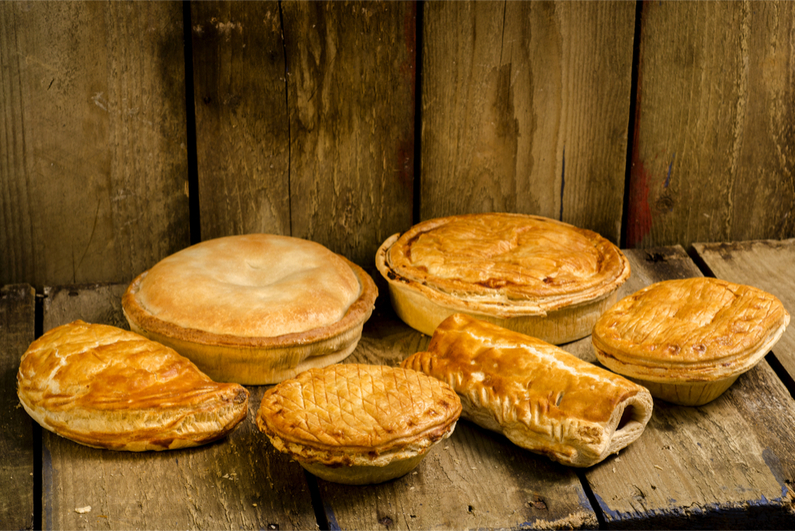 Selection of Pies, Pasties and sausage rolls on a wooden background