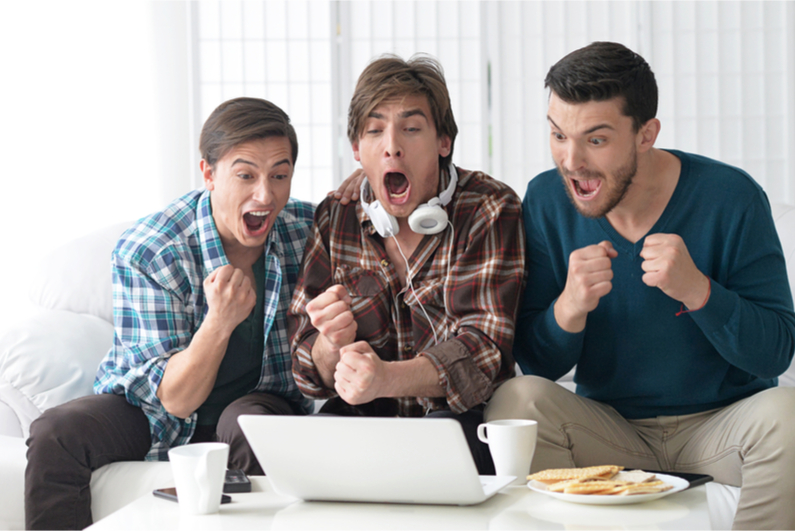 Men excitedly watching a sports event on a laptop
