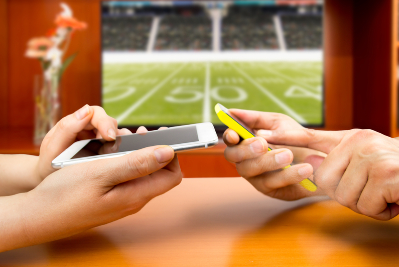 Friends using mobile phones and betting during a american football game