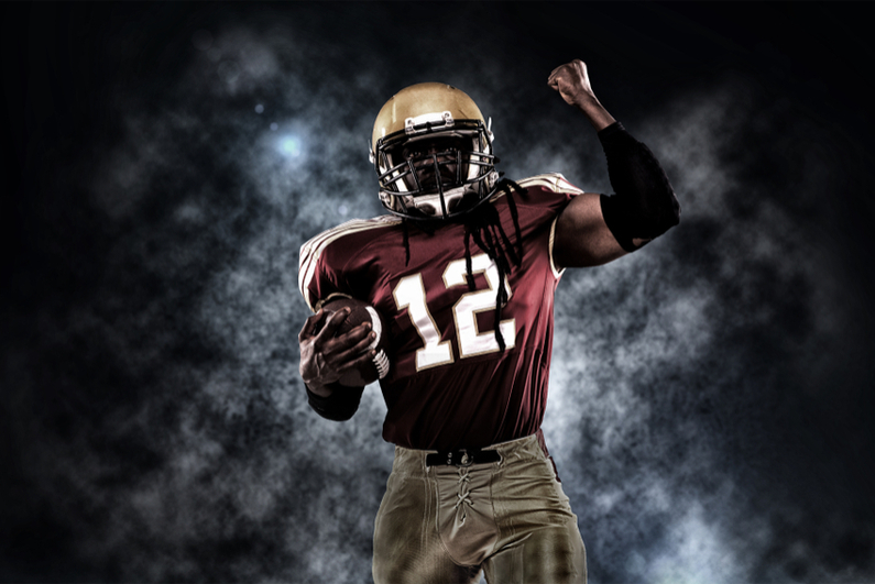 Proud American football player against a dark background