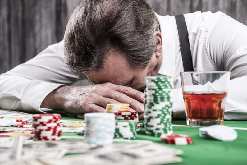 Depressed senior man in shirt and suspenders leaning his head at the poker table with money and gambling chips laying all around him