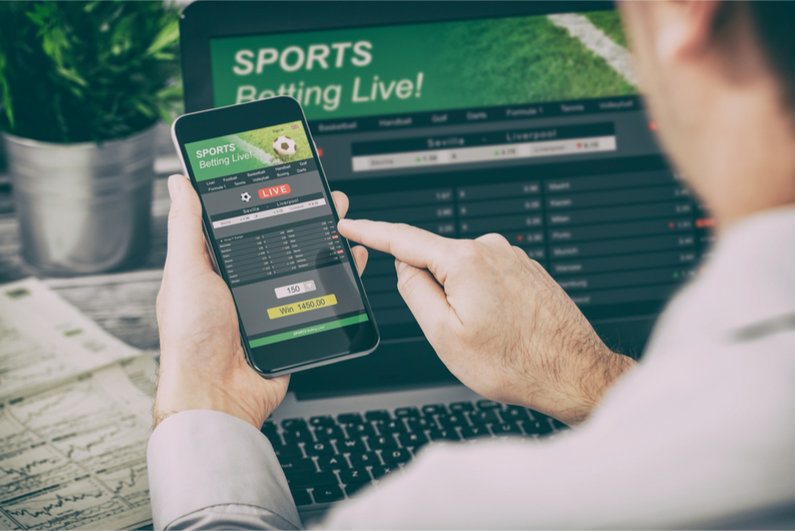 Betting on phone with laptop