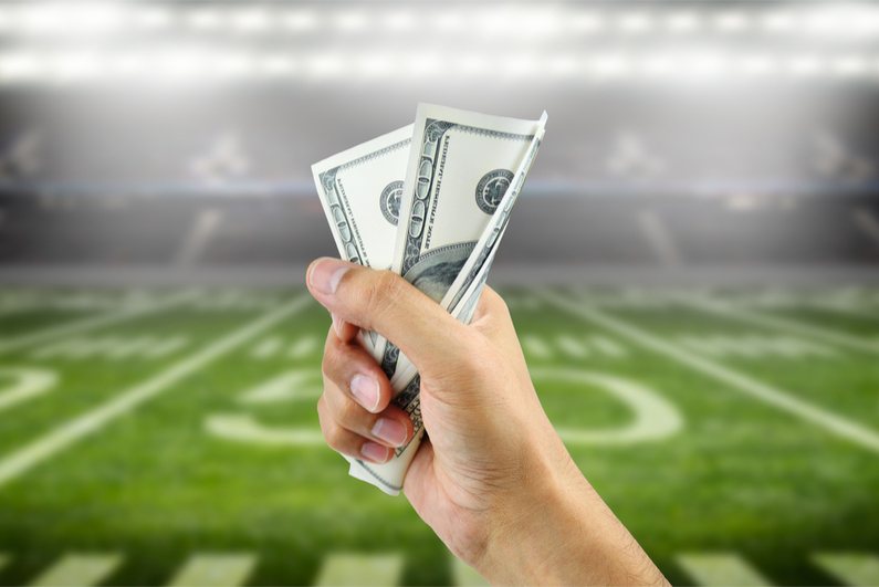 Close up of a man's hand crushing a wad of hundred dollar bills in concept of getting money with bets in American football