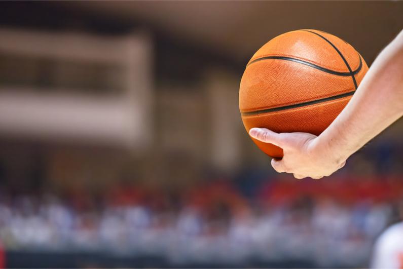 An arm holding a basketball