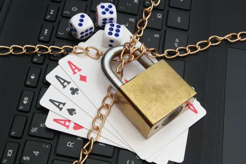 Cards, dice, and laptop keyboard with padlock