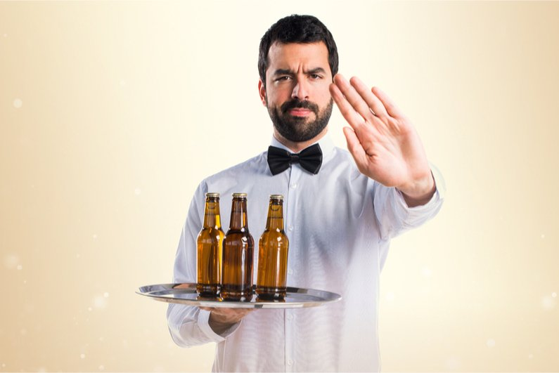 Waiter with beer bottles on the tray making stop sign