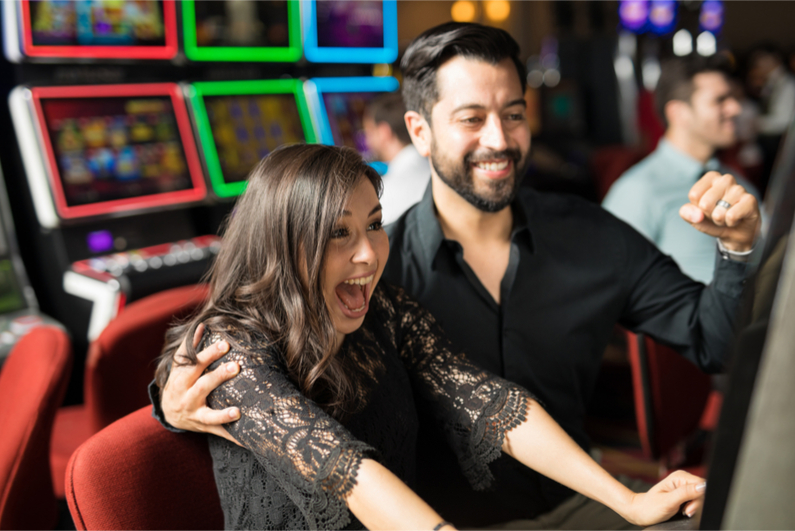 Good looking young couple celebrating and looking excited about hitting the jackpot in a slot machine