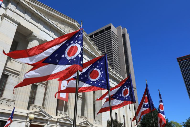 State of Ohio flags waving in front of the Statehouse in Columbus, OH