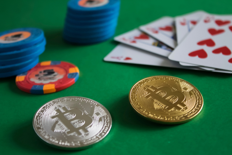 Two bitcoins on a green poker table