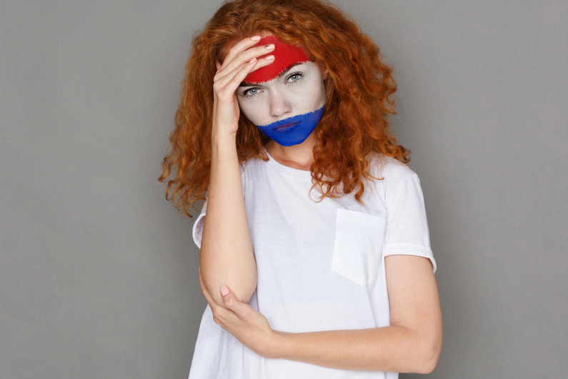 Face of young sad woman painted with flag of Holland