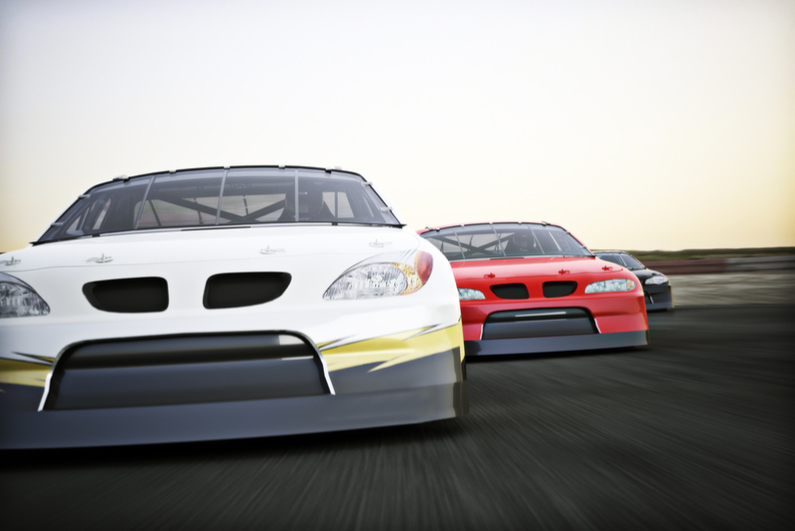 Front view of auto racing race cars racing on a track with motion blur