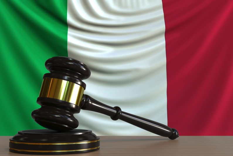 Judge's gavel with Italian flag in background