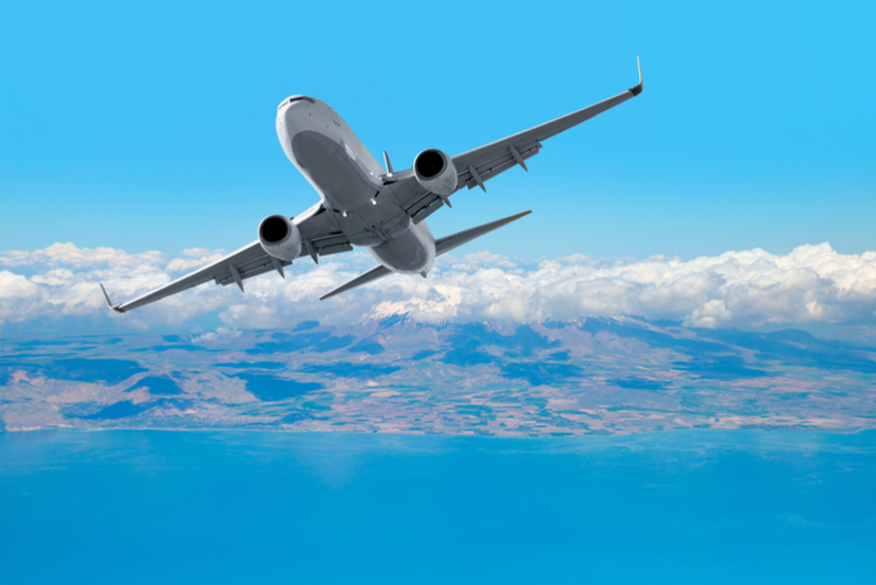 Passenger plane flying above sea against sky background
