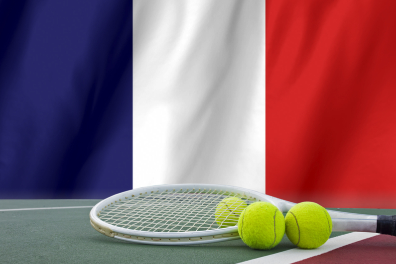 Tennis rackets and balls with French flag in background
