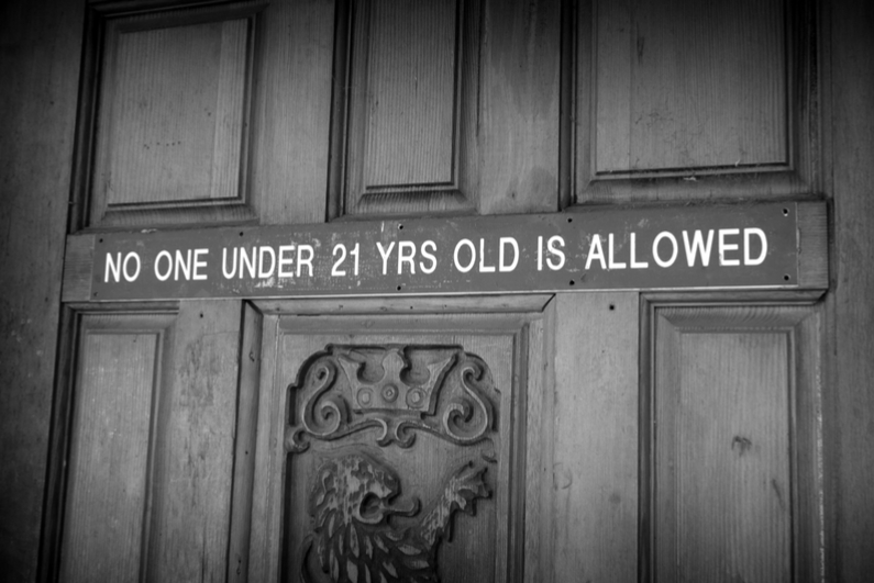 Door with sign saying NO ONE UNDER 21 YRS OLD IS ALLOWED