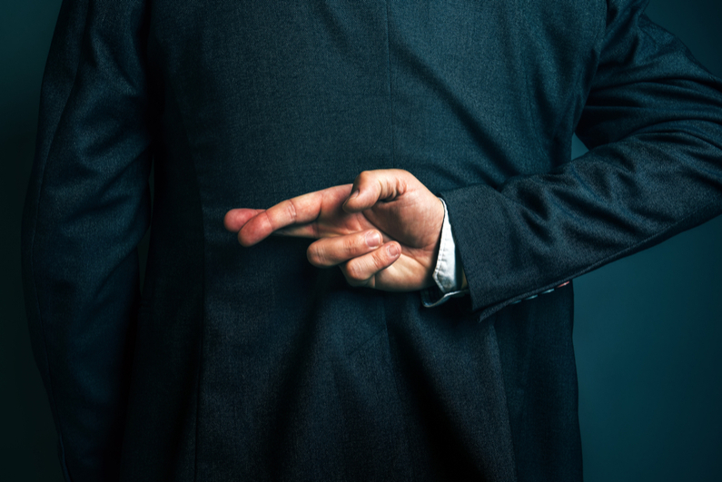 Dishonest businessman lying and holding fingers crossed behind his back