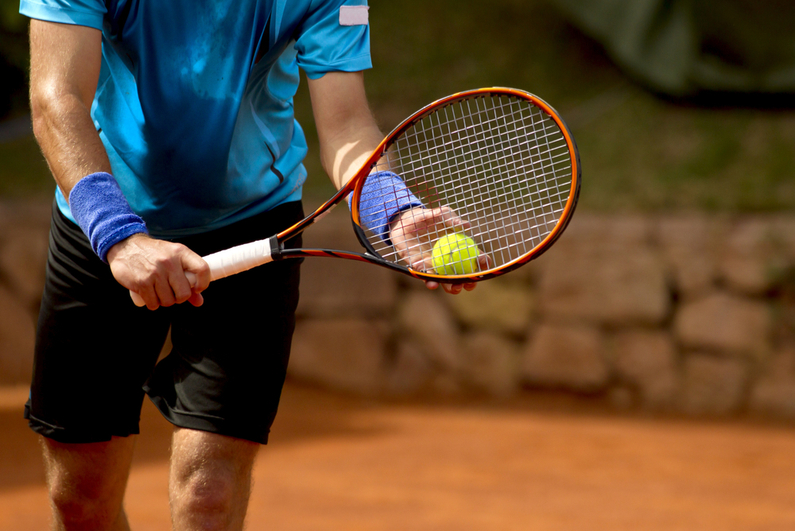 Tennis player preparing to serve.
