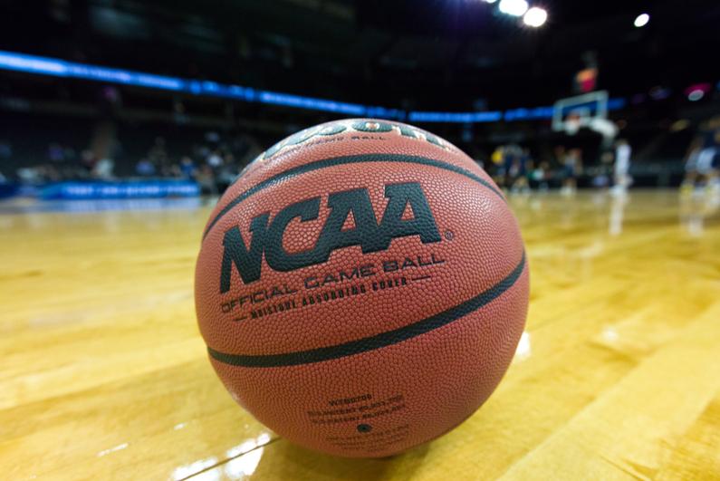 NCAA basketball sitting on a court.