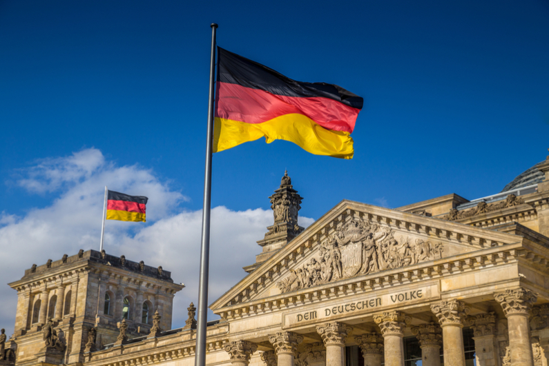 German flag waving in front of Reichstag building