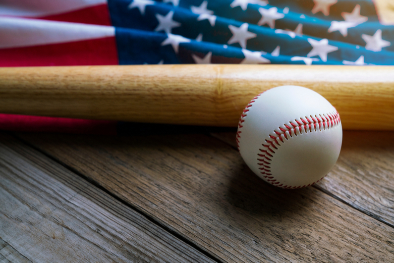 Baseball and bat with US flag in background