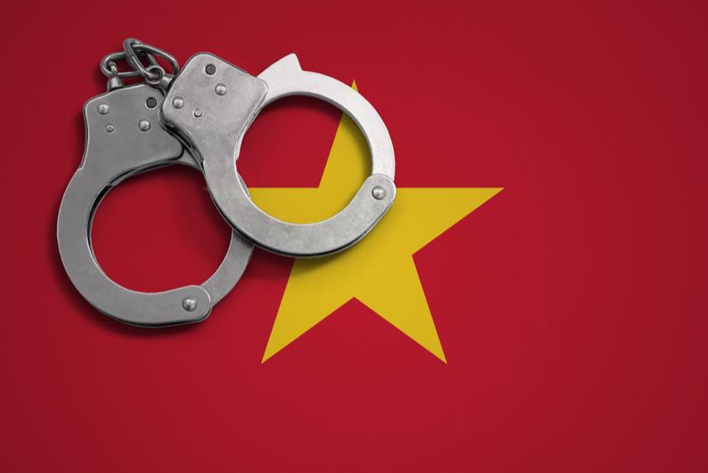 Police handcuffs on flag of Vietnam