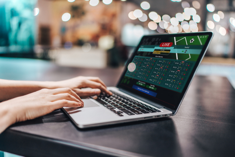 Hands of a woman placing online bets on a laptop