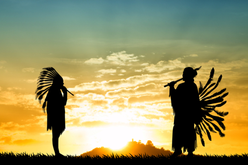 American Indians playing music at sunset