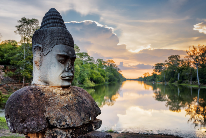 Stone asura in foreground, Cambodian sunset in background