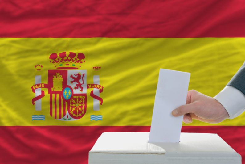 Hand putting ballot in box in front of Spanish flag