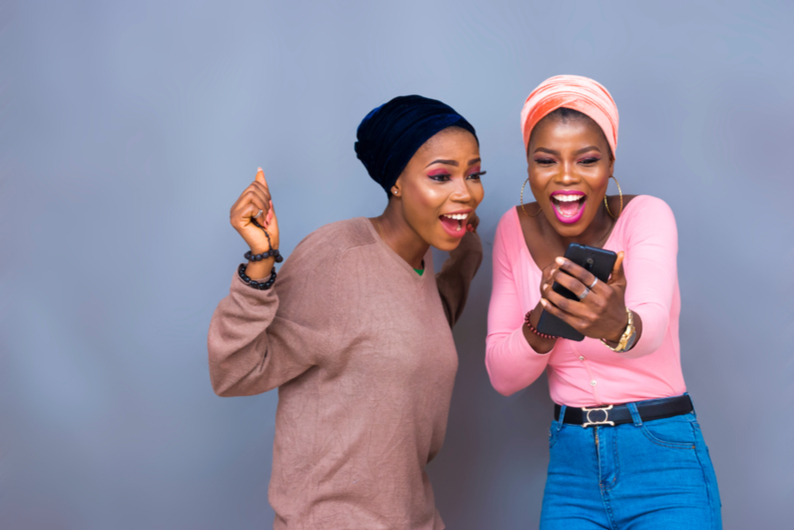 Excited black girls looking at phone