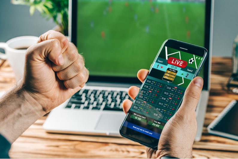 Man celebrating win with mobile phone