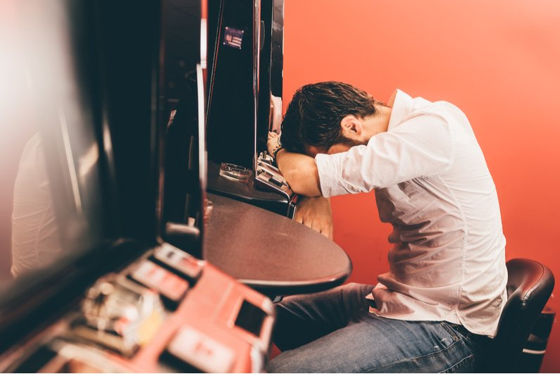 Despondent gambler at slot machine