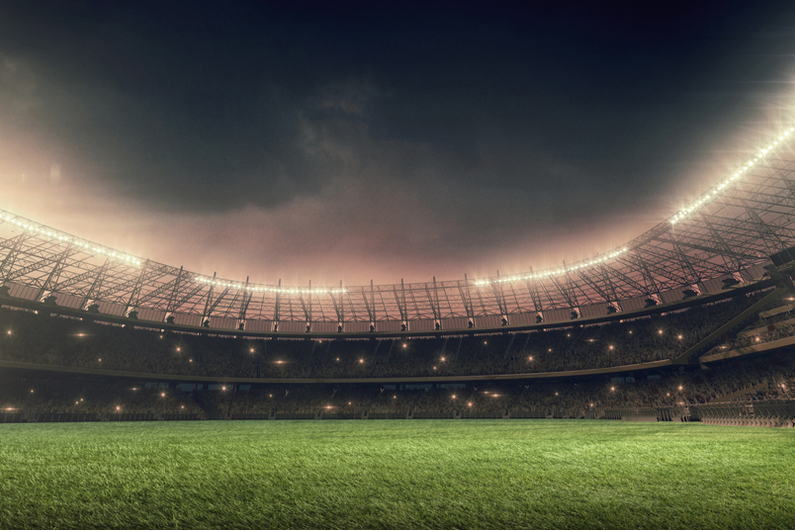 Illuminated soccer stadium under night sky