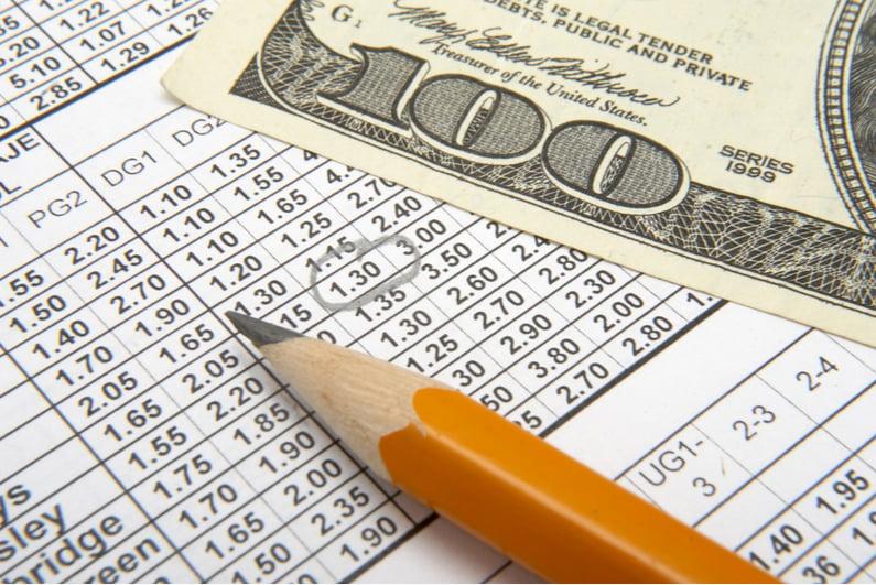 sports betting sheet and US hundred dollar bill