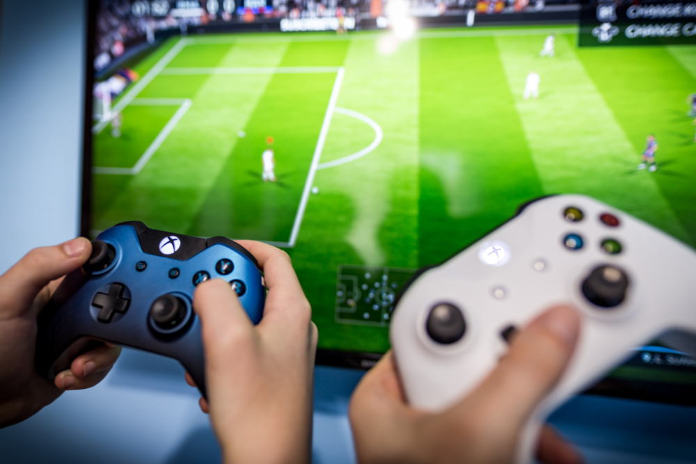 fifa game being played on screen with game consoles